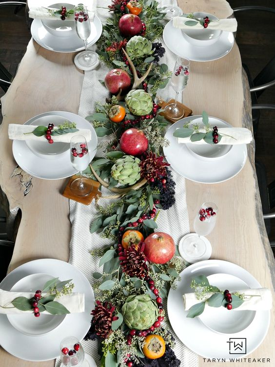 a beautiful natural Thanksgiving tablescape with a greenery runner, bold blooms, pomegranates, persimmons, artichokes and antlers