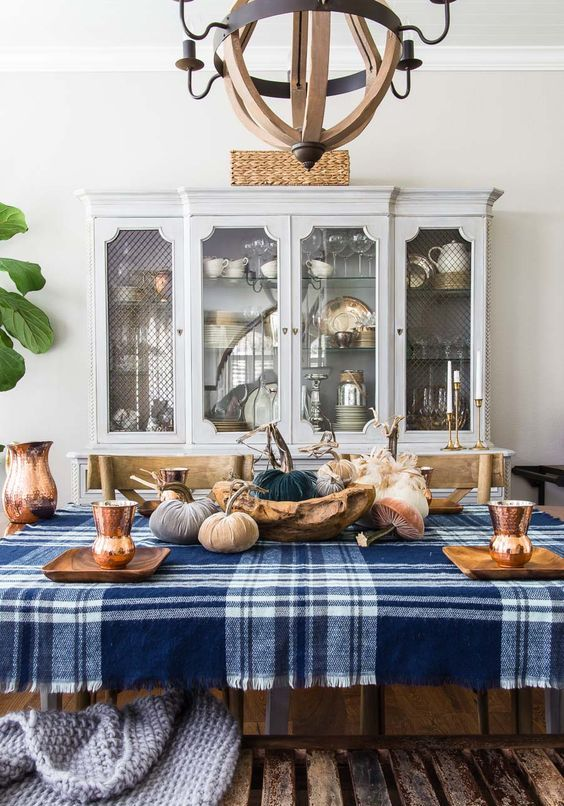 a blue plaid tablecloth and some blue fabric pumpkins make the tablescape more modern and bold