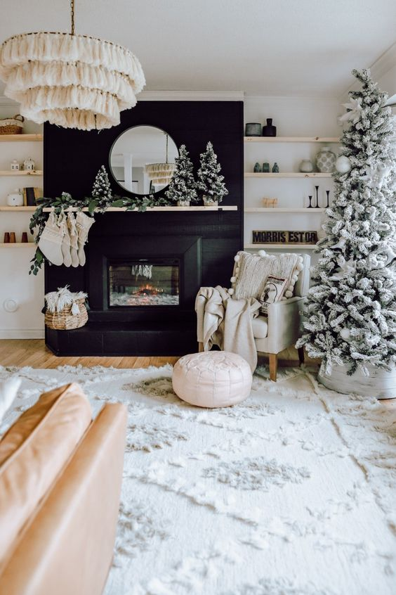 a boho farmhouse Christmas living room with a flocked tree and a cluster of such mini trees on the mantel plus stockings