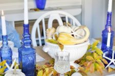 a bold blue and yellow Thanksgiving table setting with blue bottle candleholders and blue printed placemats and napkins