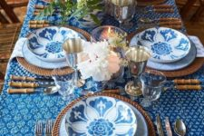 a bright Thanksgiving table setting with printed plates, a printed tablecloth, woven elements and neutral blooms