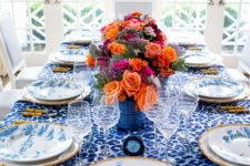 a bright blue Thanksgiving tablescape with a leopard print tablecloth, blue and whiet porcelain and super bold blooms