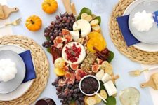 a bright modern Thanksgiving table with orange and blue touches looks super bold and super cool