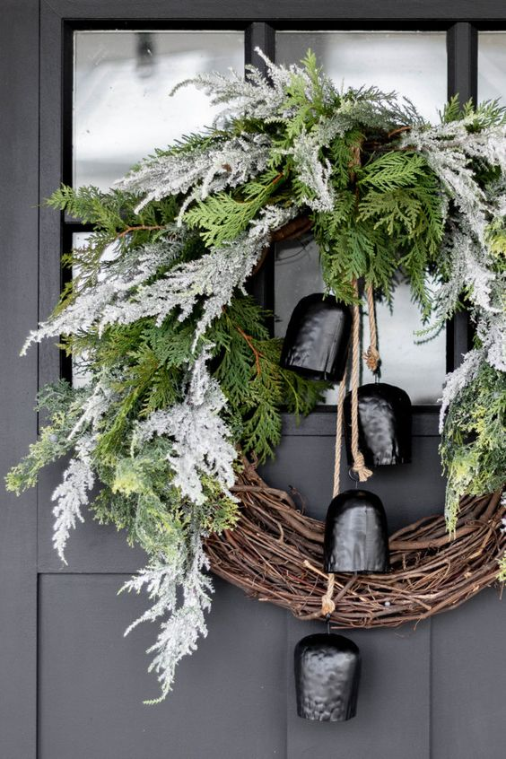 a catchy Christmas wreath of vine and flocked and usual evergreens and large black bells is a lovely and bold decoration