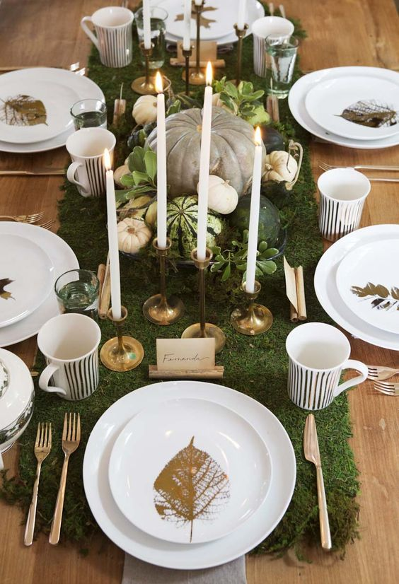 a chic Thanksgiving tablescape with a moss runner, pumpkins, greenery, candles and and gold leaves