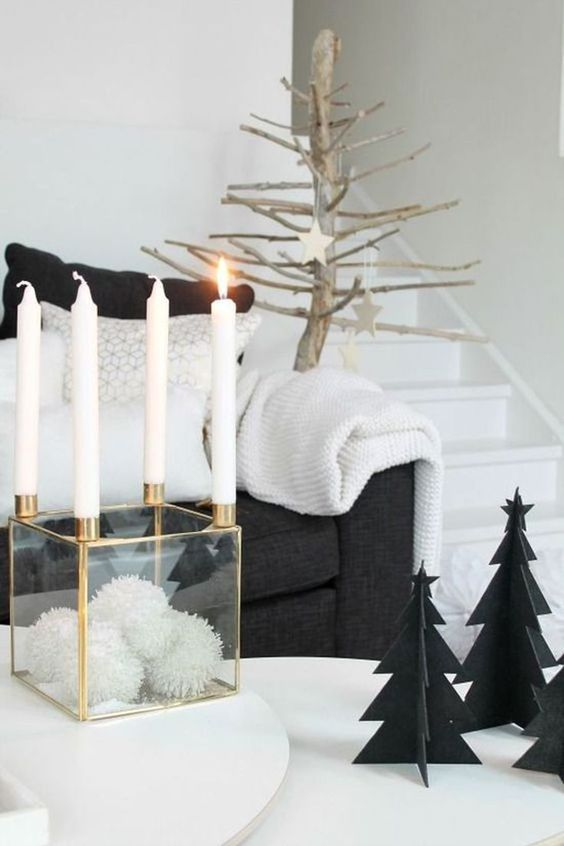 a clear box with white pompoms and candles on each corner, black cardboard Christmas trees and a tree with wooden stars