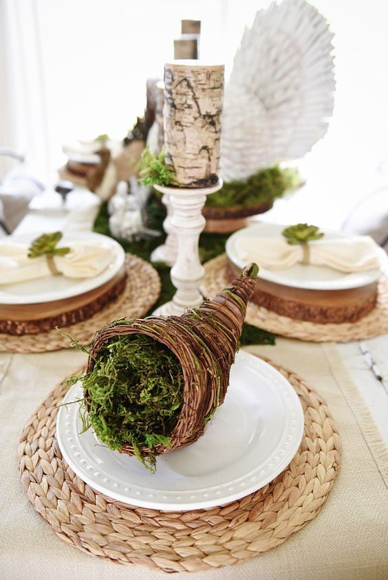 a cornucopia with moss, brich bark wrapped candles on vintage stands for a natural feel at the table