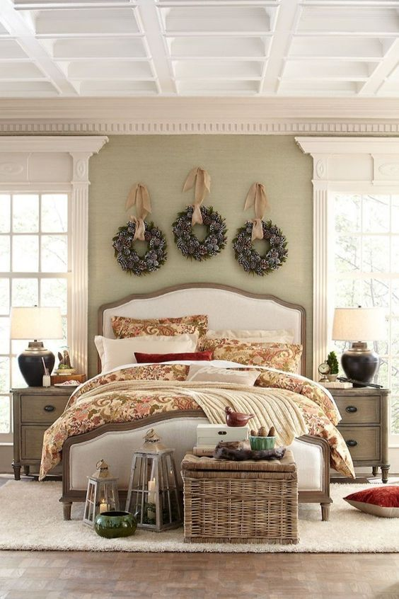a cozy Christmas bedroom with snowy evergreen wreaths over the bed, candle lanterns, a basket chest with storage
