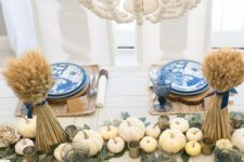 a cozy Thanksgiving table setting with woven placemats, blue plates with birds, wheat with blue ties and neutral pumpkins