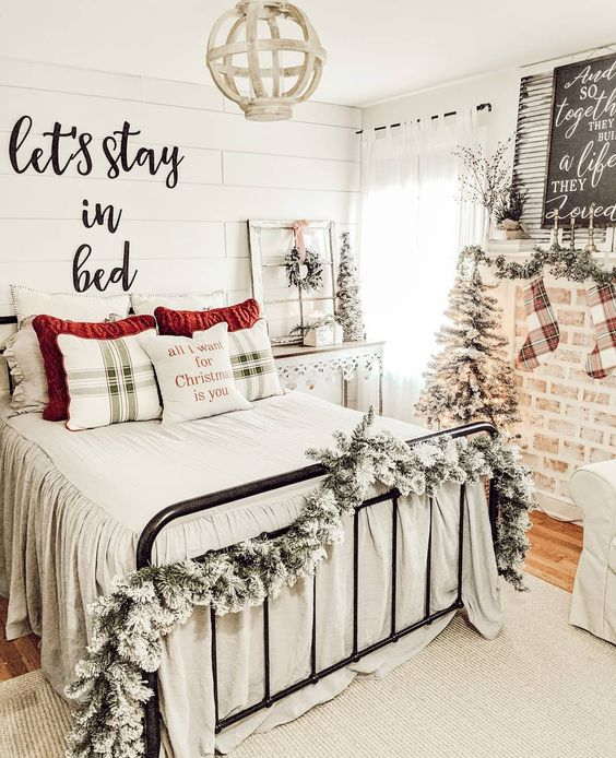 a farmhouse chic bedroom with snowy garlands, mini trees, a sign, plaid bedding and a wreath for a Christmas feel int the space