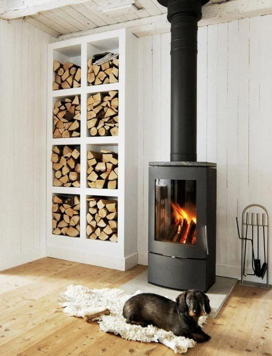 a fireplace and an open storage unit by its side make up a very cozy and chic nook and add warmth to the space