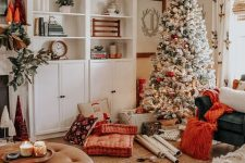 a flocked Christmas tree with lights and red and green ornaments for making your space look very holiday-like