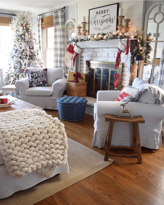a flocked fir garland, candles in wooden candleholders, printed sotckings, a flocked Christmas tree with letters and ribbons
