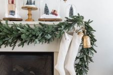 a flocked greenery garland with white stockings and a vintage bell hanging for lovely and chic Christmassy decor