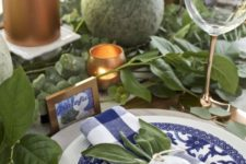a greenery and copper tablescape with blue and white plates and napkins plus cards make up a gorgeous setting for Thanksgiving