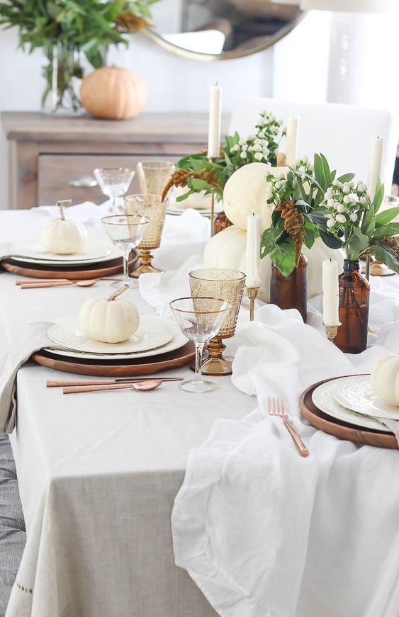 a lovely and fresh Thanksgiving tablescape with white pumpkins, lily of the valley, candles and white linens