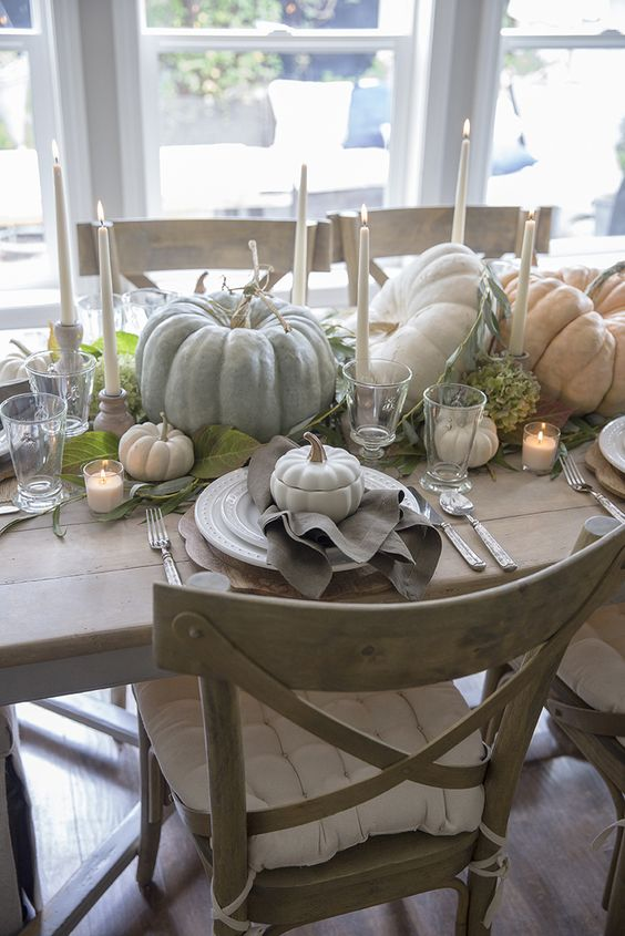 a lovely natural Thanksgiving tablescape with neutral heirloom pumpkins, tall candles, greenery and neutral linens