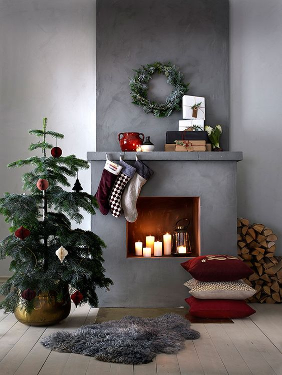a mini Christmas tree with bright ornaments, stacked pillows, bright stockings, a flocked greenery wreath and firewood