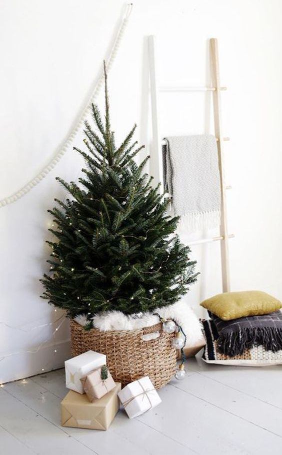 a mini Christmas tree with lights in a basket with white faux fur is a stylish and minimal idea