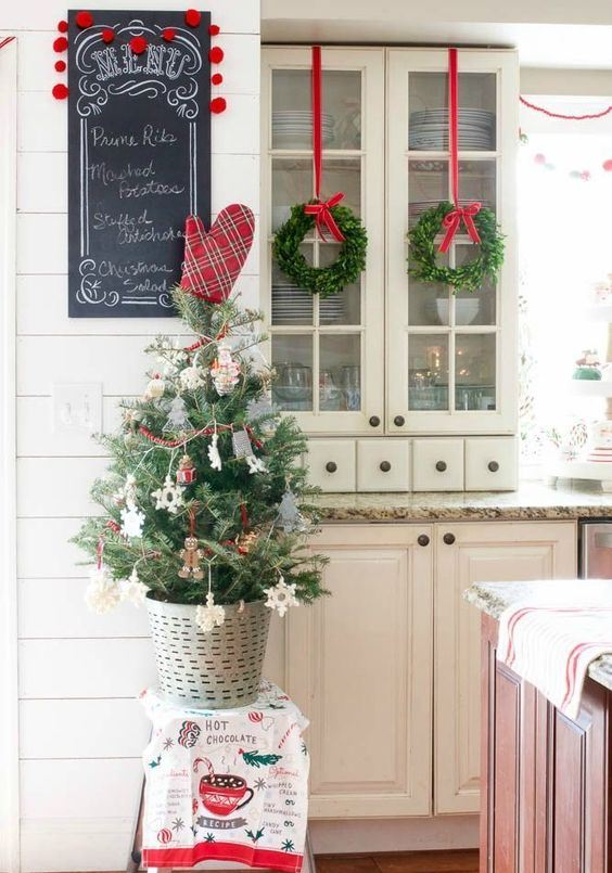 a mini Christmas tree with ornaments, a red heart and berry garlands plus evergreen wreaths with red ribbons