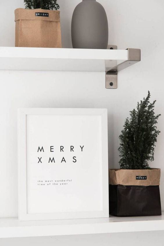 a minimalist Christmas artwork and a potted Christmas tree in a paper bag
