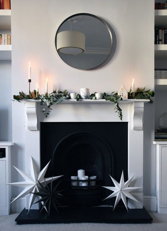 a minimalist Christmas mantel decorated with magnolia leaves and eucalyptus plus white candles and black and white stars