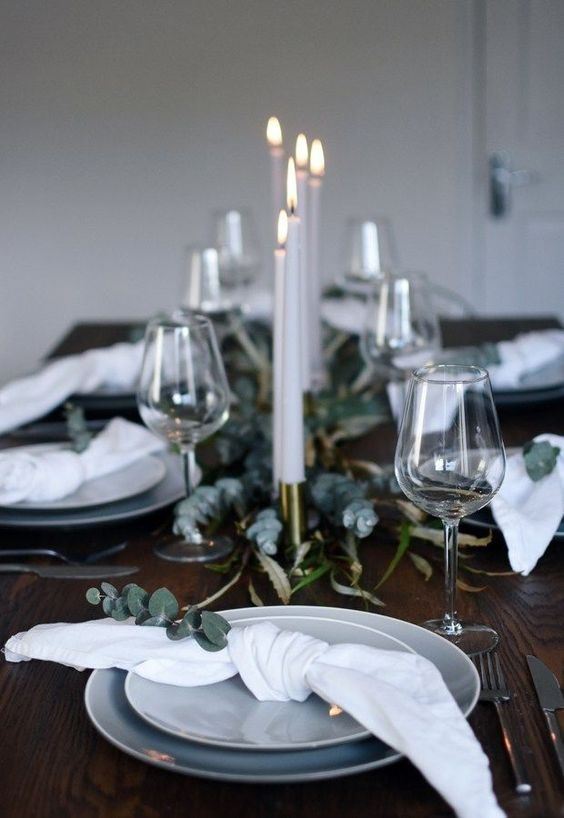 a minimalist Christmas table with eucalyptus, white napkins and grey plates plus candles