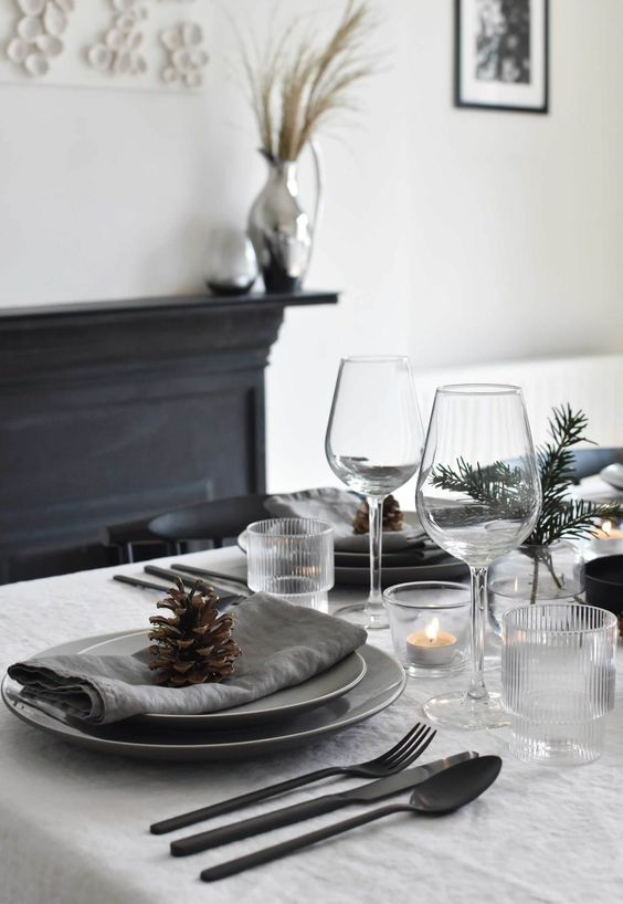 a minimalist Christmas table with grey napkins, evergreens and candles in glass candleholders plus black cutlery for a stylish look