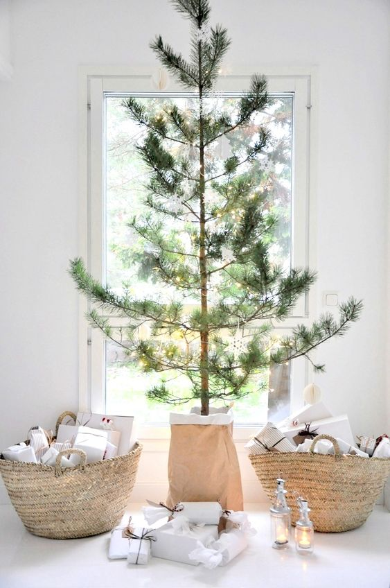 a minimalist Christmas tree with lights only, basket bags filled with gifts and some candle lanterns under the tree
