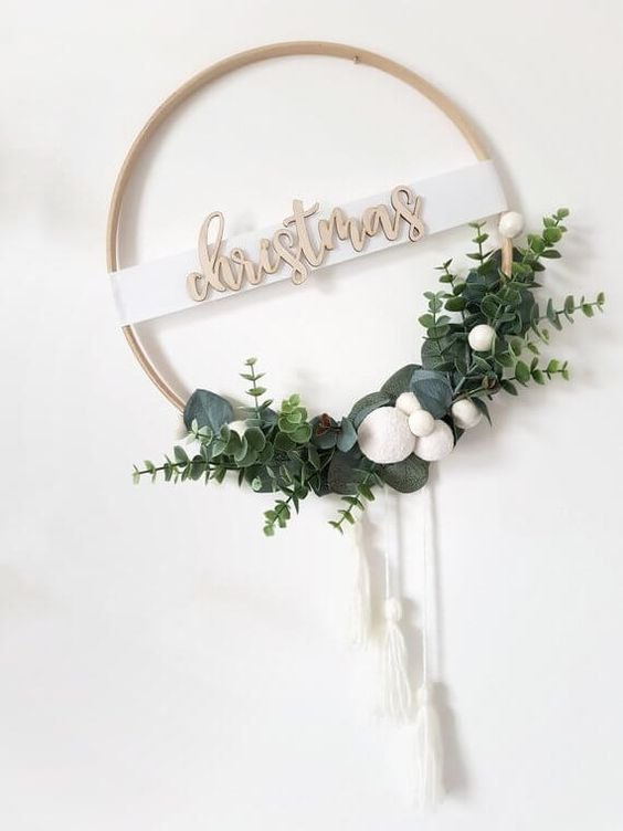 a minimalist Christmas wreath of an embroidery hoop, greenery, white pompoms and white tassels