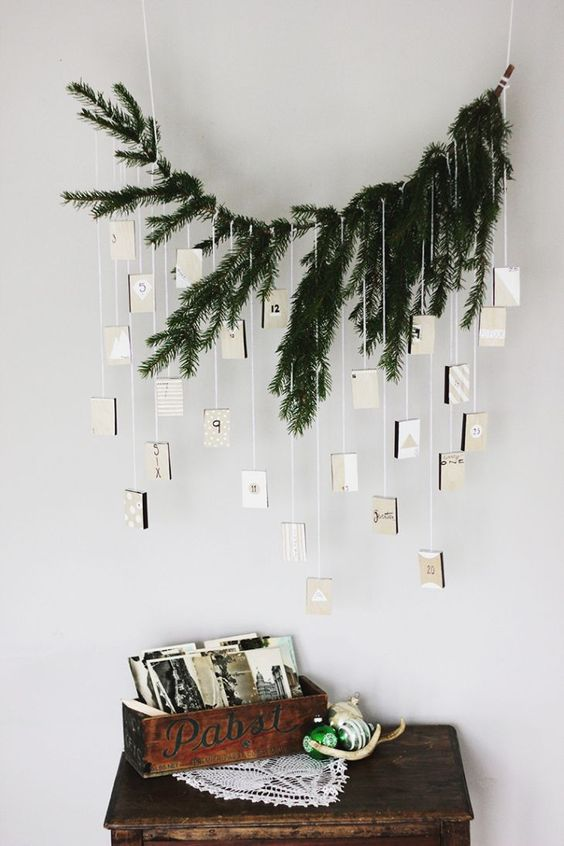 a minimalist advent calendar with evergreens and suspended boxes for each day looks rustic and minimal
