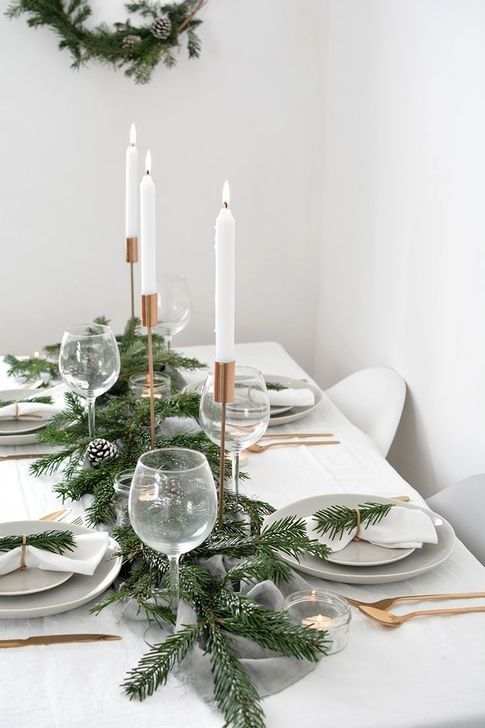 a minimalist and natural Christmas table with an evergrene garland and pinecones, gold cutlery and copper candleholders