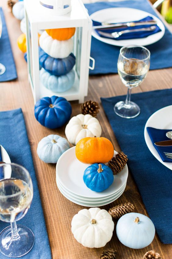 a modern Thanksgiving tablescape with bold blue placemats and light and bold blue pumpkins is a chic idea