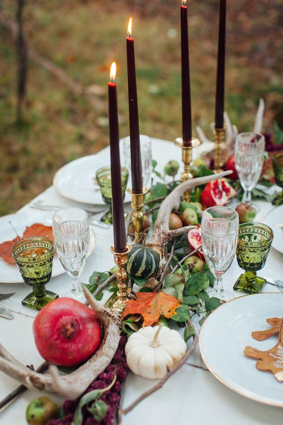 a natural Thanksgiving table runner of greenery, antlers, pumpkins and pomegranates plsu burgundy candles