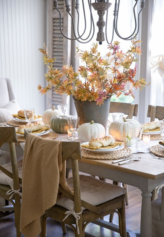 a natural Thanksgiving tablescape with neutral pumpkins, fall leaves, candles and woven chargers is a lovely idea
