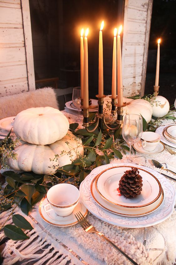 a natural Thanksgiving tablescape with white pumpkins, tall candles and a greenery runner plus pinecones is chic
