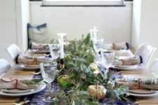 a navy and white table runner with pearls, napkins with blue edges and lots of fresh greenery for a modern and simple tablescape