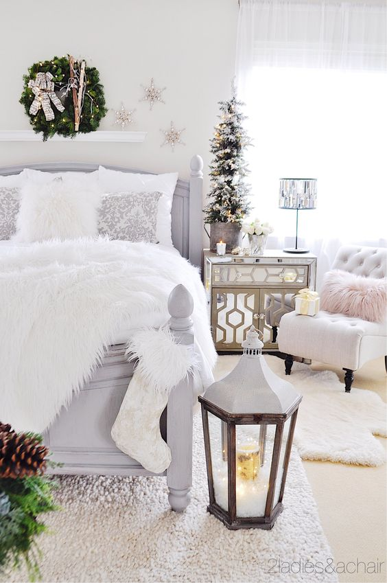 a neutral Christmas bedroom with a snowy mini tree, an evergren wreath with skis, a stocking, an oversized lantern and a faux fur blanket