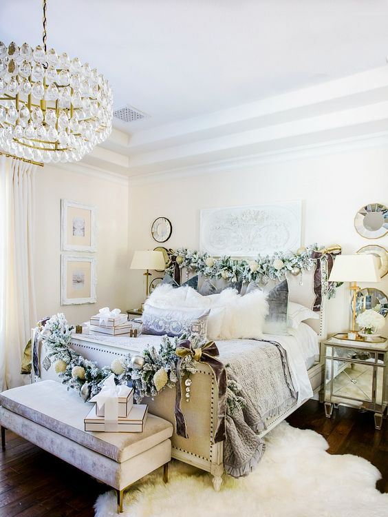 a neutral Christmas bedroom with pale greenery garlands with ornaments, gift boxes, white blooms for a refined and chic look