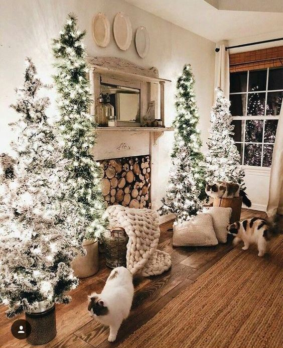 a neutral farmhouse living room with a fireplace with firewood, a cluster of flocked Christmas trees and some pillows and blankets
