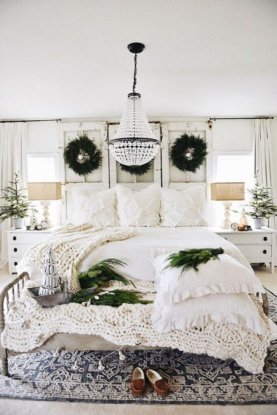 a neutral shabby chic Christmas bedroom with evergreen wreaths, garlands, knit blankets and mini Christmas trees