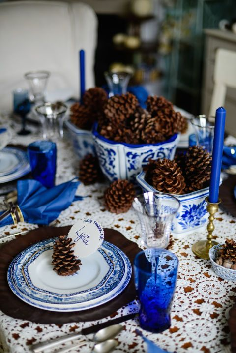 a non-typical Thanksgiving tablescape with bold blue glasses, napkins, candles and porcelain looks jaw-dropping