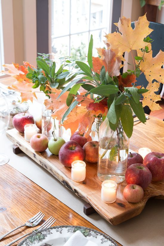 a pretty fall or Thanksgiving centerpiece of apples, fall leaves and candles on a wooden board is lovely