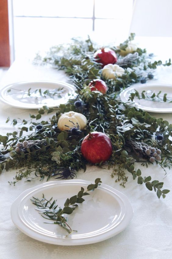 a pretty greenery table runner with pomegranates, white pumpkins, thistles and berries is amazing for Thanksgiving