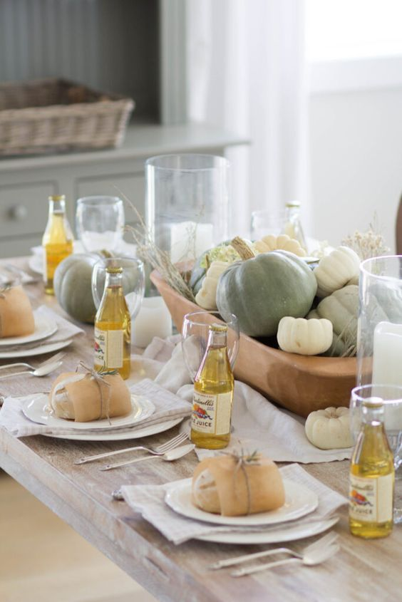 a pretty neutral Thanksgiving tablescape with a bowl filled with pumpkins and more pumpkins around looks chic