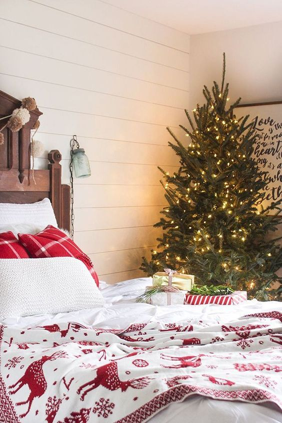 a red and white bedding set, a Christmas tree with lots of lights, pompom garlands and gift boxes right on the bed