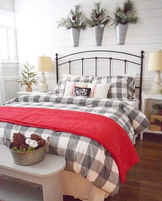 a red knit blanket, plaid bedding, snowy evergreens, pinecones and ornamnts for a warming up and cozy feeling in the bedroom