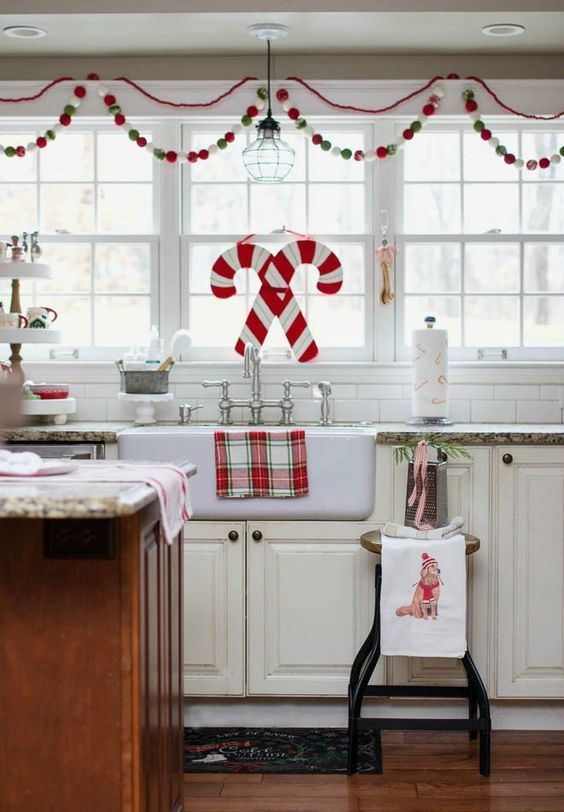 a red, white and green pompom garland, candy cane decor and plaid textiles for Christmas