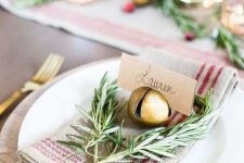 a rustic Christmas place setting with a striped napkin, twigs, a bell that holds a card is amazing for holidays