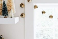 a simple garland of gold Christmas bells is a lovely and chic idea that will easily bring festive spirit to the space